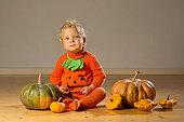 Small boy in pumpkin costume posing at studio