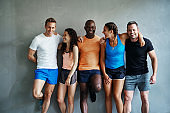 Laughing friends in sportswear standing together in a gym