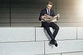 Stylish man with newspaper sits on brickwall