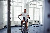 Mature man pushing himself during a stationary bike workout