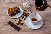 Top view of a bowl with sugar cubes, coffee beans, a piece of amazing cake on a saucer and a cup of coffee, anise and chocolate bar on bright wooden background