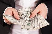 Businesswoman counts money in hands.