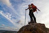 Woman hiker standing on mountain peak