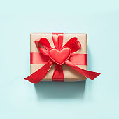 Valentine's day card. Gift with red ribbon and heart on blue surface. Top view. Square.