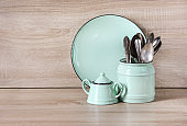 Turquoise crockery, tableware, dishware utensils and stuff on wooden table-top. Kitchen still life as background for design.  Image with copy space.