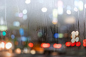 City life, road wit cars in the city trough the window during heavy rain