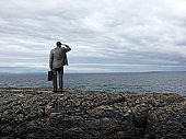 Businessman Stands On Rocky Cliff Overlooking Ominous Sky And Rough Sea