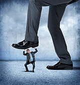 Large Businessman About To Step On Small Businessman