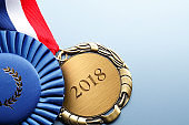 """Close Up Of Medal Engraved With """"2018"""" On Blu Background"""