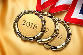 Three Stacked Gold Medals Engraved 2018, 2017, And 2016 On Gold Satin