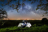 Woman using her laptop in the camping at night. Woman sitting in the tent under trees and beautiful night sky full of stars and milky way. On the background luminous city. Long exprose