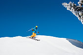 Freeride skier riding down the slope in the mountains copyspace powder snow movement motion active lifestyle seasonal concept