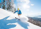 Shot of a professional skier skiing in the mountains on fresh powder snow on a beautiful sunny winter day on the winter resort
