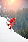 Male snowboarder freerider in a red suit riding from the top of the snowy hill with snowboard in the evening at sunset. Skiing and snowboarding concept