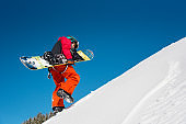Low angle full length shot of a fully equipped snowboarder climbing up the snowy slope, carrying his snowboard copyspace nature outdoors winter recreation seasonal sport active lifestyle concept