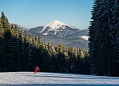 Man skier skiing downhill at ski resort against forest and mighty mountains. Male is wearing orange ski-suit, helmet and goggles. Carpathian Mountains, Bukovel