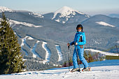 Cheerful woman skier smiling joyfully to the camera while skiing in the Carpathians mountains at winter ski resort Bukovel, Ukraine on sunny day copyspace recreational active lifestyle concept