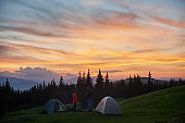 Man and woman having a rest in the camping near two tents in the mountains while hiking together with their backpacks enjoying beautiful sunset with fiery colorful sky love relationships nature.