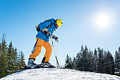 Low angle shot of a skier wearing riding equipment standing on top of the hill in the mountains at ski resort people lifestyle recreation sports sportsman hobby vacation holidays season