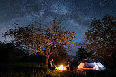 Happy couple tourists - man and woman sitting at a campfire near tent under trees and beautiful night sky full of stars and milky way. Night camping. Long exprose
