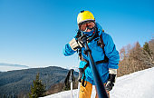 Shot of a man skier wearing ski equipment taking a selfie using monopod at the winter resort. Blue sky and winter forest on the background technology youth recreation activity