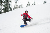 Male snowboarder riding down from the mountain in winter day