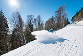 Professional skier shoting by action camera on selfie stick while skiing on fresh powder snow in the mountains at winter ski resort Bukovel active lifestyle sport recreation technology movement