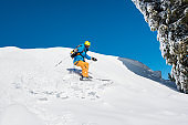 Male freerider skier riding downhill the slope in the mountains copyspace powder snow movement motion active lifestyle seasonal concept