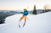 Skier man riding on fresh snow on the slope of mountain on the winter resort