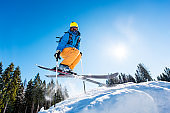 Low angle shot of a skier in colorful gear jumping in the air while skiing on a slope copyspace sunlight extreme adrenaline enjoyment recreation activity concept