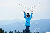 Woman skier enjoying skiing at ski resort in the mountains