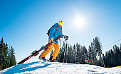 Male skier walking up the snowy hill in the mountains carrying his ski equipment. Beautiful sunny winter day copyspace nature active lifestyle winter resort leisure concept