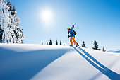 Low angle shot of a skier walking on top of the mountain with his skis on his shoulder on a sunny winter day sunlight nature recreation skiing lifestyle downhill sportive concept