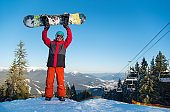 Full length shot of a snowboarder standing on the top of the mountain at winter ski resort, holding up his snowboard in the air above his head, smiling to the camera copyspace ski lift sport concept