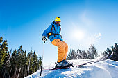 Rearview shot of a skier enjoying skiing the slope at ski resort in the mountains on a sunny winter day copyspace seasonal activity sport sportsman hobby recreation travel concept