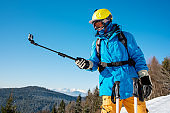 Shot of a skier in winter clothing taking a selfie using monopod for his camera. Blue sky and winter forest on the background skiing activity sports concept