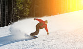 Male snowboarder slides down from the mountain in winter day