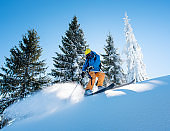Shot of a professional freeride skier skiing in the mountains on a sunny winter day nature recreation active sportive hobby lifestyle sports concept