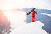 Male snowboarder standing on the top of the snowy hill, holding snowboard in hand, smiling to the camera, showing thumbs up. Ski season and winter sports concept