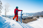 Professional snowboarder standing on top of a slope looking around enjoying the view on winter ski resort Bukovel in the sunny morning copyspace mountains landscape lifestyle concept