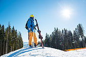 Full length shot of a skier standing on top of a snowy slope in the mountains looking around enjoying beautiful sunny winter day. Winter resort