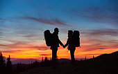 Happy couple hiking together holding hands standing with their backpacks on top of a mountain during stunning sunset people love silhouettes meadow active relationships