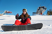 Happy snowboarder girl sitting in the snow near a ski lift against a blue sky and showing thumbs up gestures of good class, Bukovel
