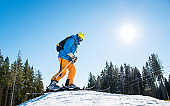 Low angle shot of a skier getting ready to riding, standing on top of the hill in the mountains at ski resort people lifestyle recreation sports sportsman hobby vacation holidays season