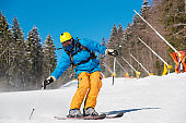 Full length shot of a skier riding on the slope at the winter resort in the Carpathians mountains extreme lifestyle sportspeople enjoyment sportswear seasonal recreation resort