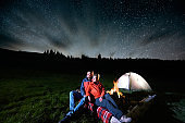 Night camping in the mountains. Romantic couple tourists sitting at a campfire near illuminated tent under beautiful night starry sky. Long exposure