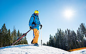 Skier walking in the mountains carrying his ski equipment copyspace nature active lifestyle resort leisure concept