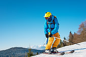 Man skier in colorful gear skiing on fresh powder snow in the mountains copyspace ski resort recreation travelling tourism vacation extreme adrenaline