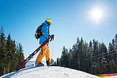 Full length shot of a skier walking on the top of the snowy slope, carrying his ski equipment copyspace nature active lifestyle resort leisure concept