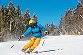 Male skier skiing in the mountains copyspace ski resort. Blue sky and winter forest on the background. recreation travelling tourism vacation extreme adrenaline